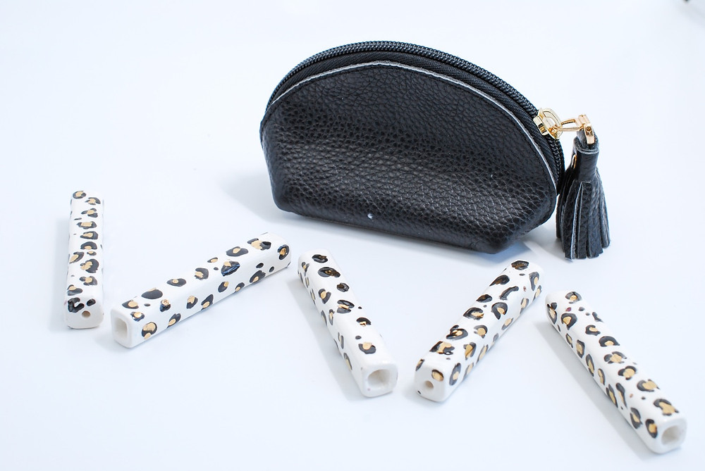 Handcrafted gold leopard print ceramic pipes displayed in a zig-zag pattern and shown with a small black pouch