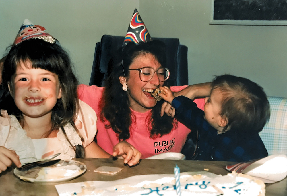 two young children and a mom eating cake and celebrating a birthday