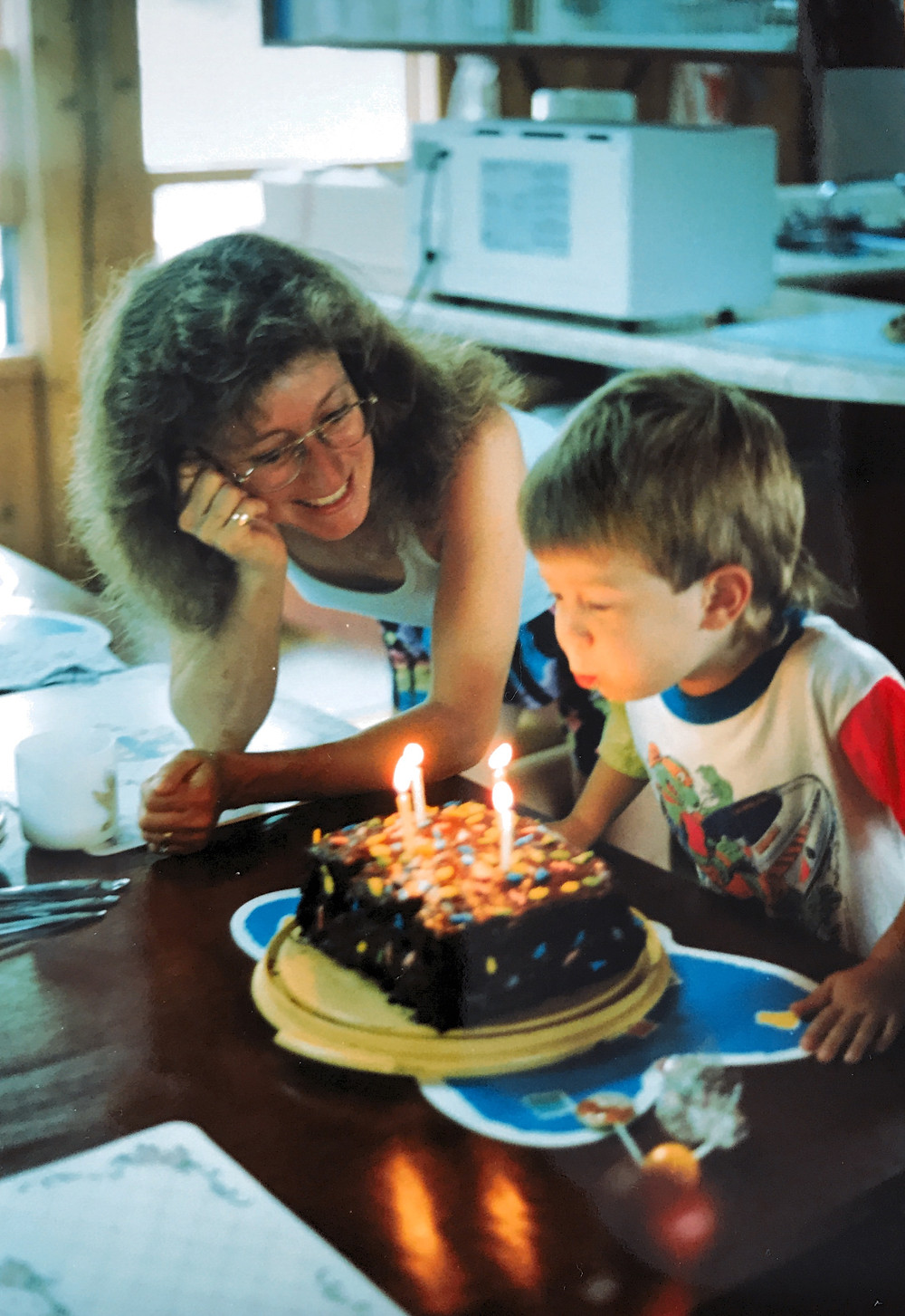 Mom with young boy blowing out candles on a cake