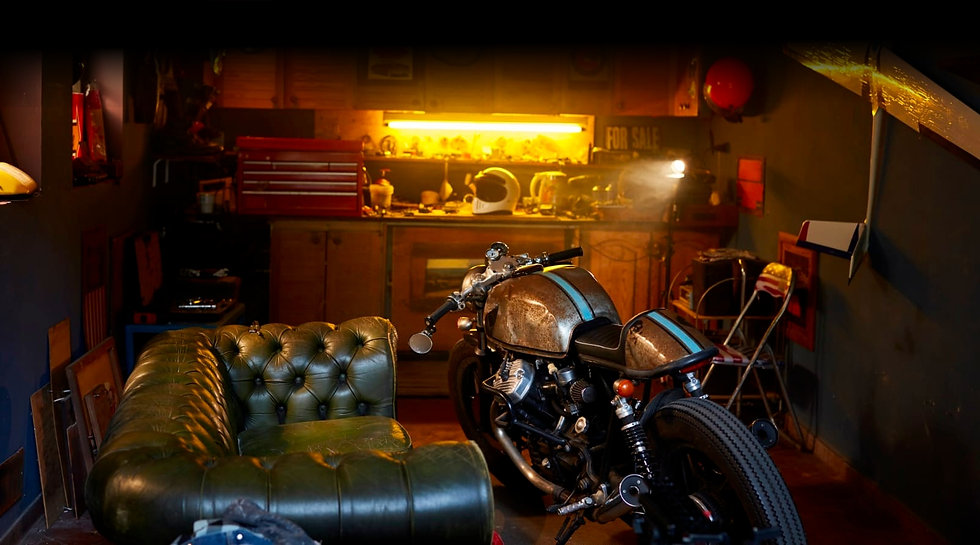 Motorcycle in a garage with weatherd leather couch.