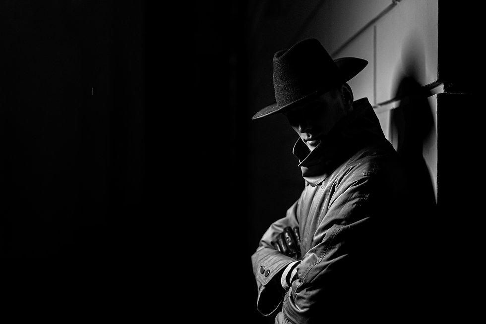 dark silhouette of a man in a raincoat w