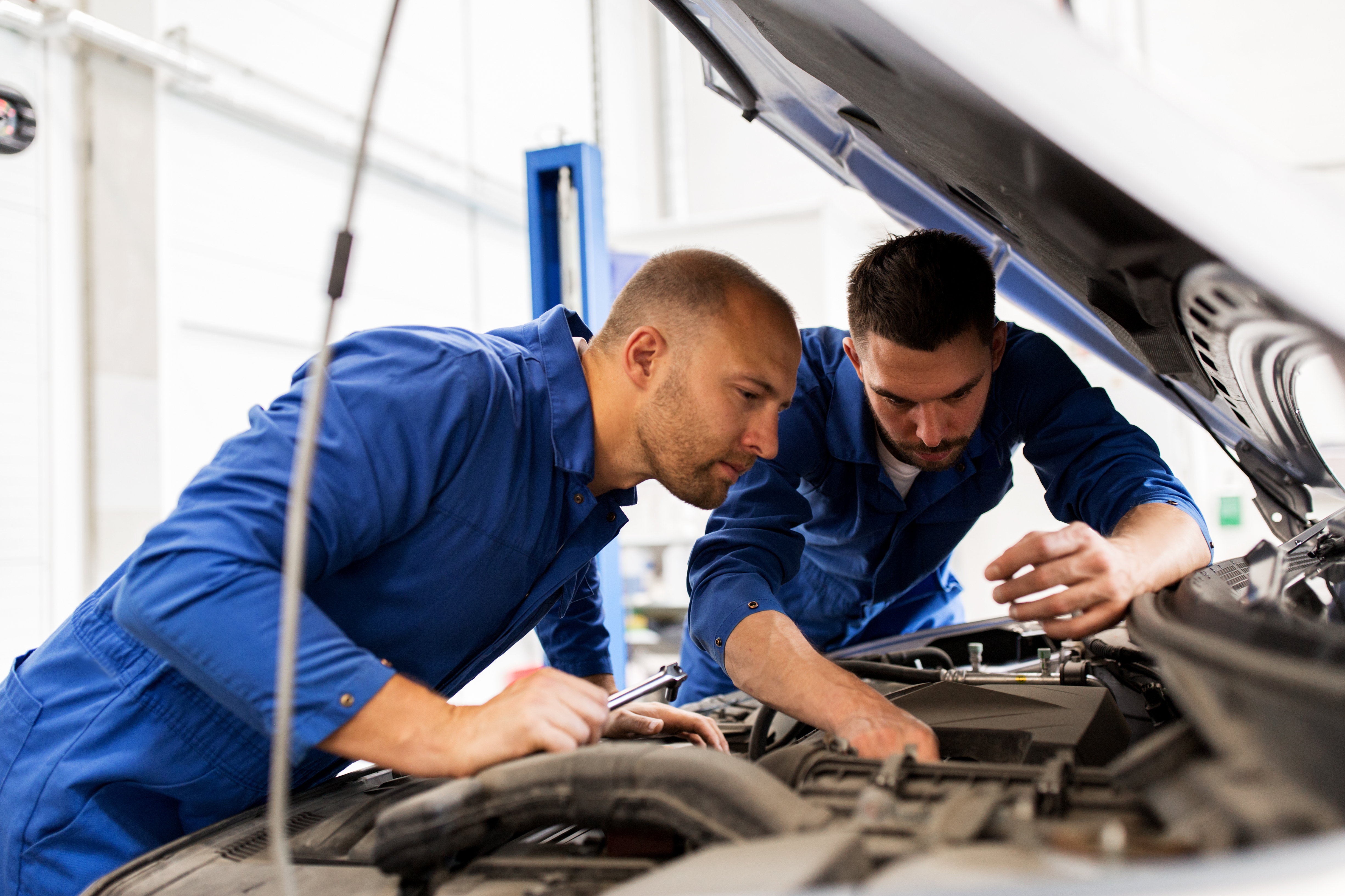 auto service, repair, maintenance and people concept - mechanic men with wrench repairing car engine