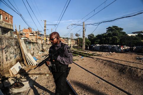 A cop walks over the train line at Jacarezinho Slum. Rio de Janeiro, 01/18/18
