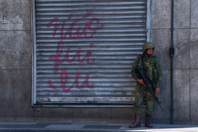 """A soldier patrols a street in downtown Rio with a sign written """"it wasn't me"""" during the Olympics in Rio. 06/13/2016"""