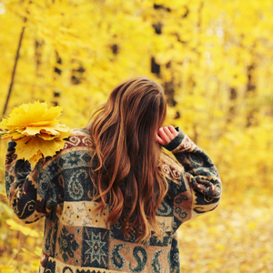 Woman in thick, colorful sweater in forest full of trees and leaves that have turned yellow in fall.