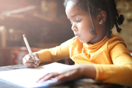 Profile of little African girl writing  at home..jpg