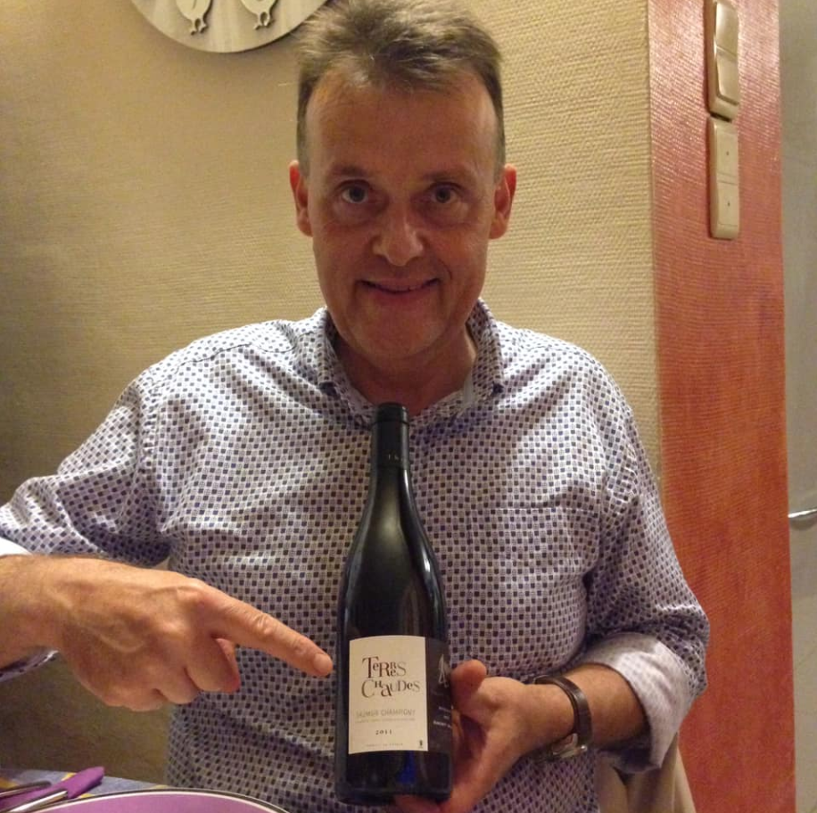 Michel holding a bottle of Terres Chaudes by Thierry Germain
