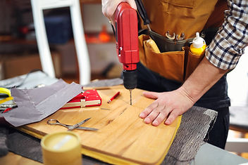 person drilling hole in wood