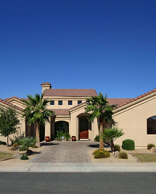 Front of mission style home with plam trees and grass lawn