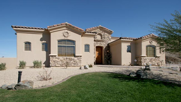 Front of classic stucco home with stone features and grass lawn