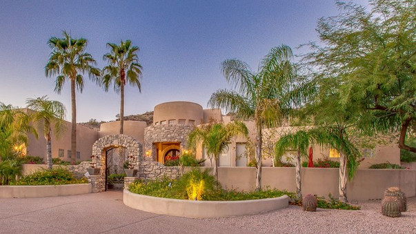 Front of phoenix stucco-style custom home with palm trees