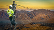 Lineman (Or Lineworker or Engineer) In A Remote Desert Landscape Fixing A Telephone Line.j