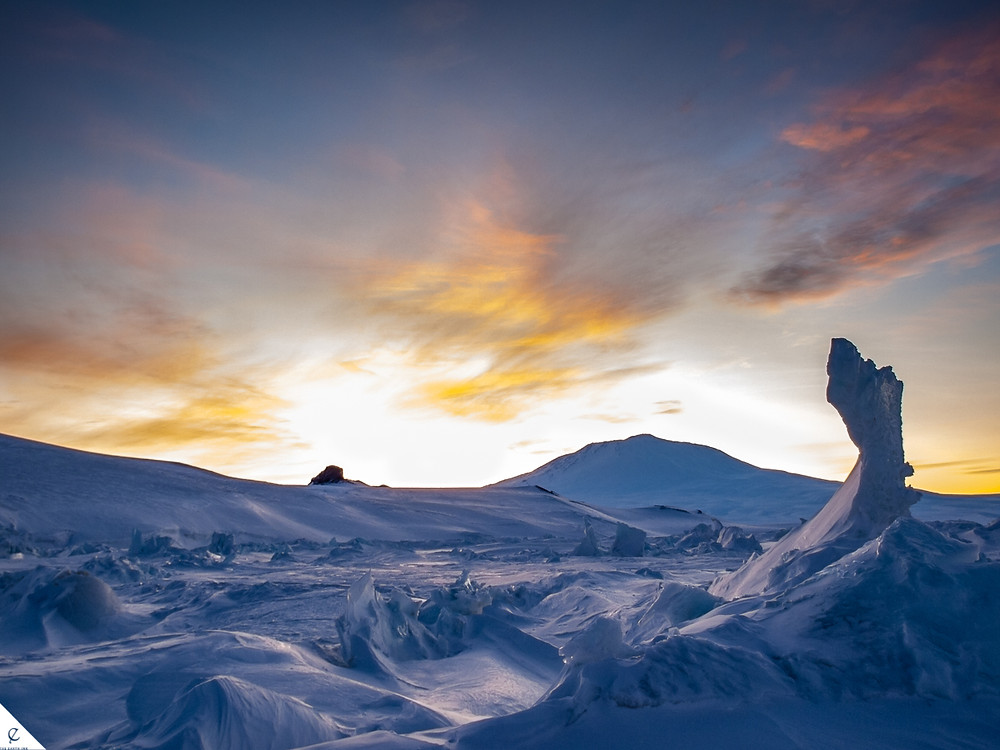 Exploring ice, snow, and cold weather on the Ross Sea Ice Shelf in Antarctica with Castle Rock and the volcano, Mount Erebus, in the background. Also nearby: Scott Base (New Zealand) and McMurdo Station (USA).