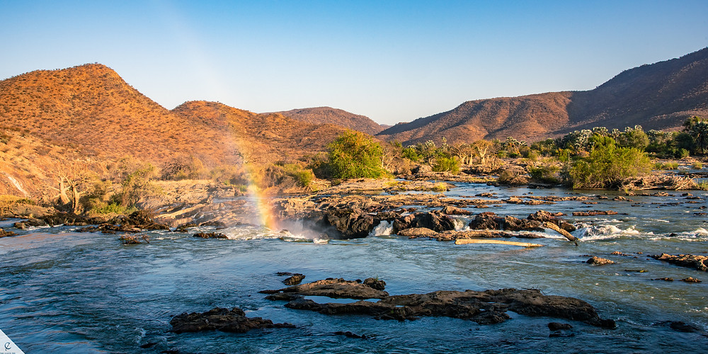 The top of Epupa Falls at sunrise with a beautiful rainbow rising in the mist, Namibia.