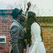 man-in-hat-kissing-woman-in-white-dress-