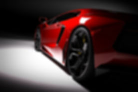 Red fast sports car in spotlight, black background. Shiny, new, luxurious. 3D rendering.jpg