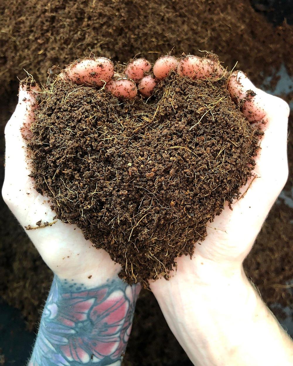 Mandi Warbington Co Owner of On The Grow, LLC holding Hydroponic Microgreens grow Medium Cococoir in the shape of a heart