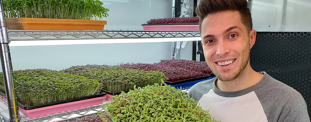 Cj Vaughn of On The Grow holding a Bootstrap Farmer tray of Microgreens in front of our Microgreens grow rack