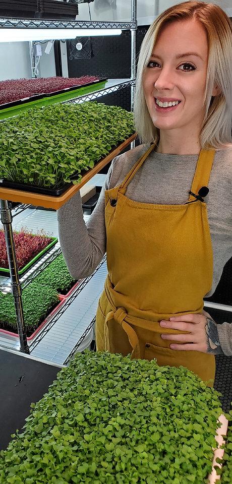 Mandi Warbington of On The Grow, LLC holding a Bootstrap Farmer tray full of Broccoli Microgreens