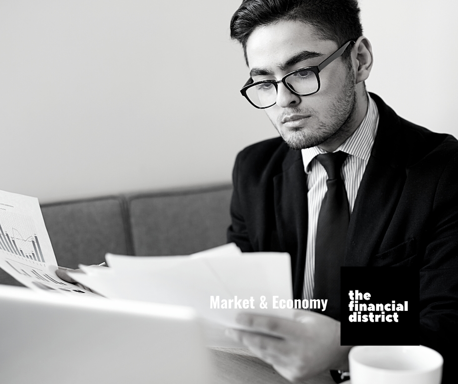 Market & economy: Market economist in suit and tie reading reports and analysing charts in the office located in the financial district.