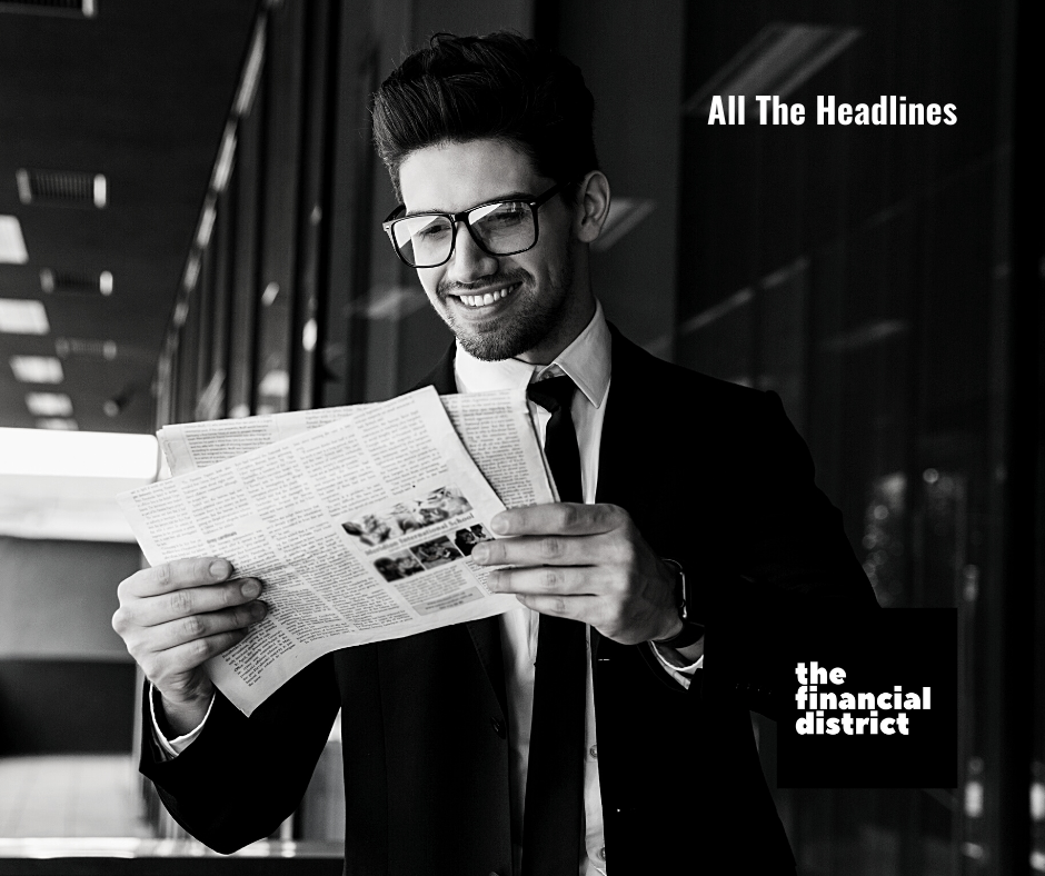 All the news: Business man in suit and tie smiling and reading a newspaper near the financial district.