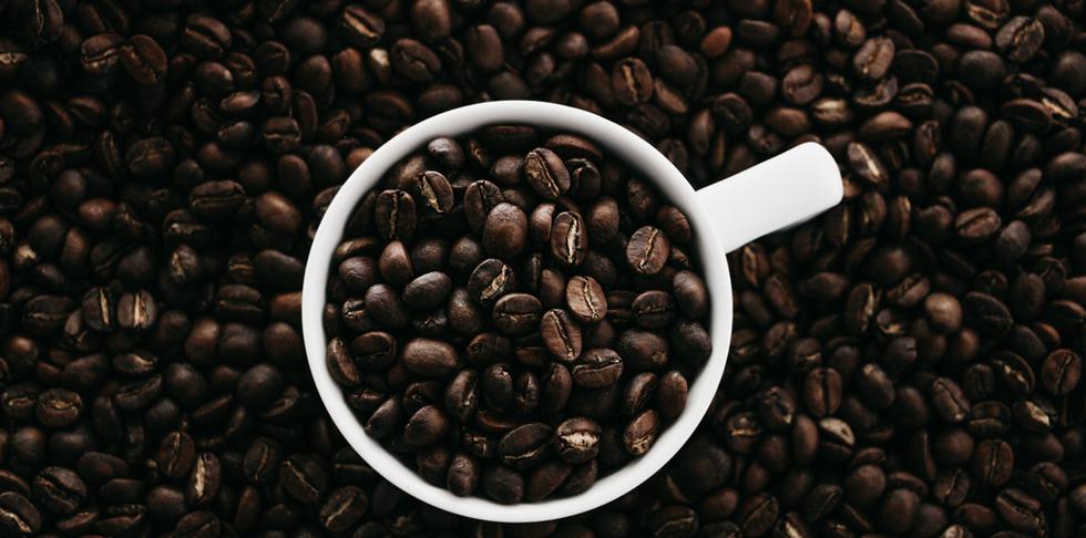 Taza sobre grano de café.png