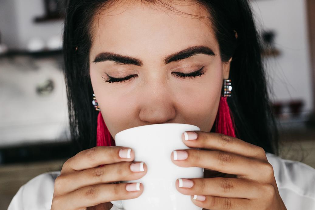 Acercamiento de persona tomando café.png