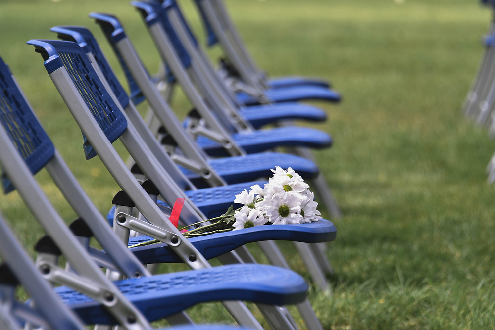 Flowers on one of the empty chairs, left by family members of a husband and father who died from COVID-19 two days prior.