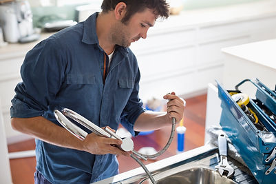 Technician repairs and installs new chrome modern kitchen faucet