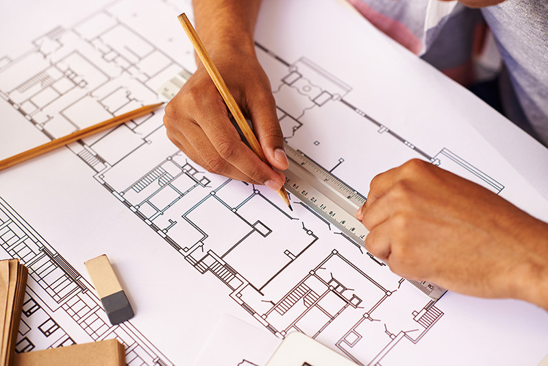 homem desenhando e dimensionando um projeto arquitetônico