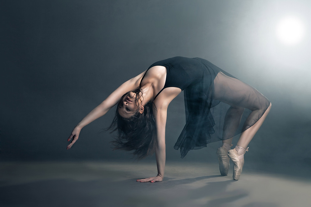Modern female dancer bending backwards in studio