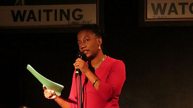 Teri wears a read sweater and is reading a poem at Busboys and Poets in Washington D.C.