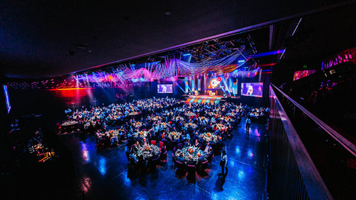 Event photography: gorgeous room setup of gala dinner table and stage.