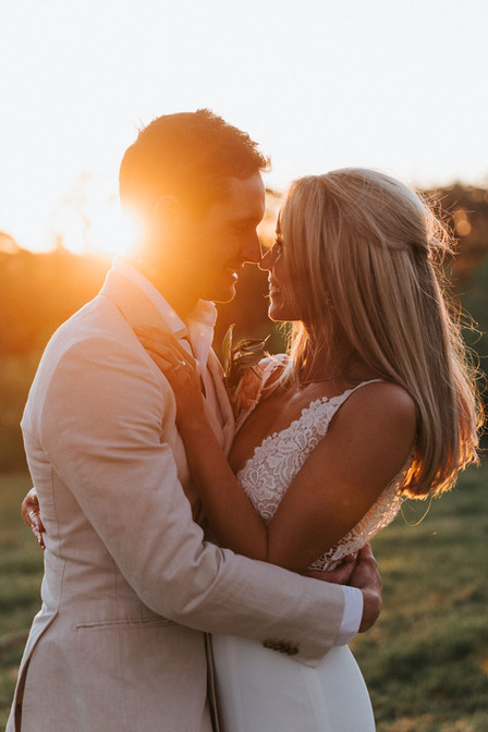 Beautiful wedding photography of a couple embracing at sunset on a farm.