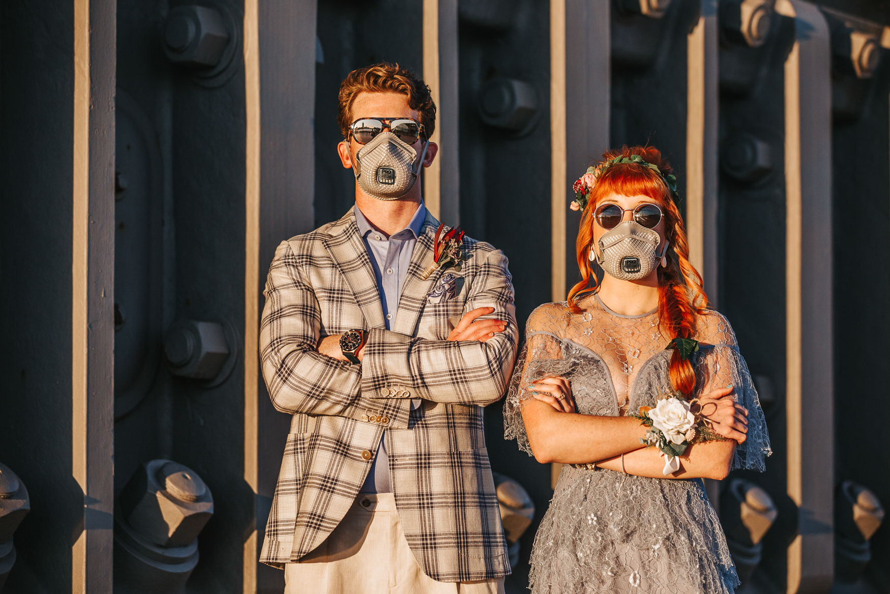 A married couple wear face masks at their elopement wedding.g