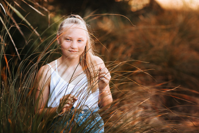 Sydney family photography of a young girl in a grass field at sunset.