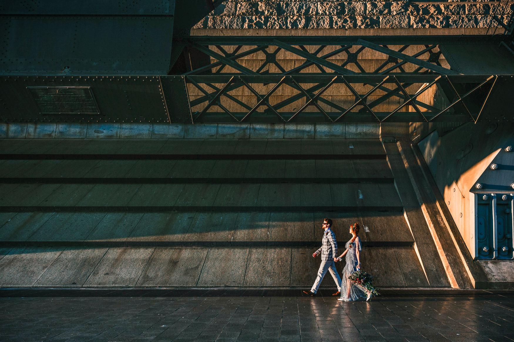 Bride and groom walk under Sydney Harbour Bridge.