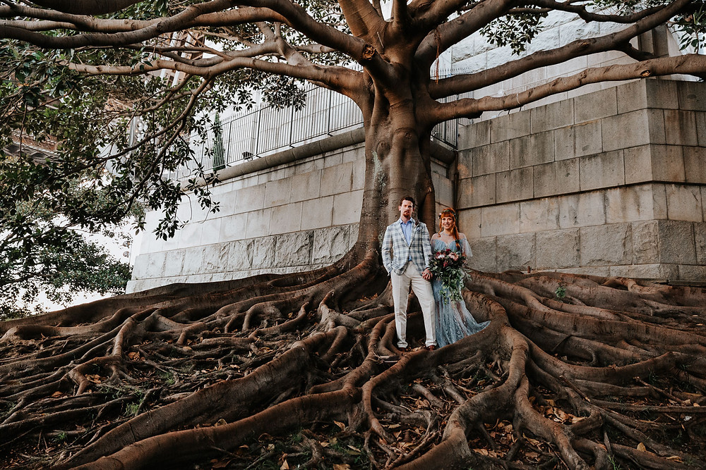 Photo of married couple standing under a tree.