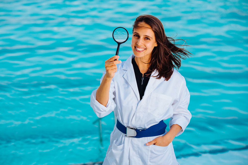 Creative corporate portrait photography: A marine biologist in a lab coat poses in front of Bondi Icerbergs swimming pool.
