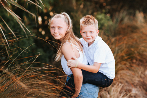 Childrens photography of a brother and sister in a grass field.