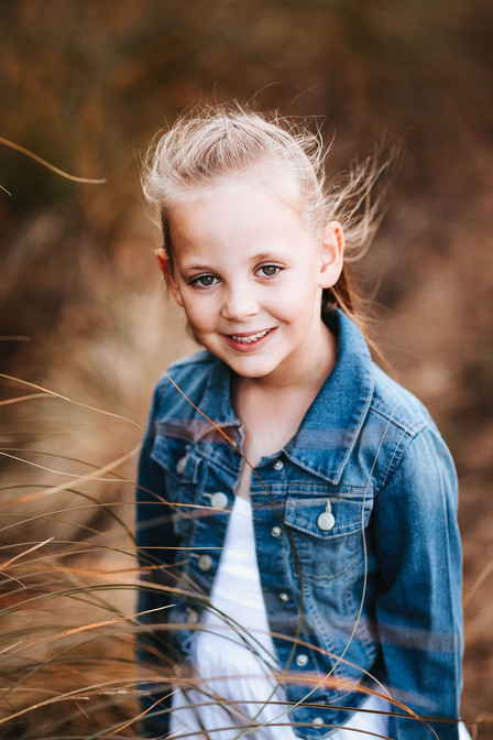 Cute sydney childrens portrait photography of a girl in a grass field at sunset.