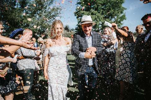 Candid wedding photography of a couple showered in confetti.