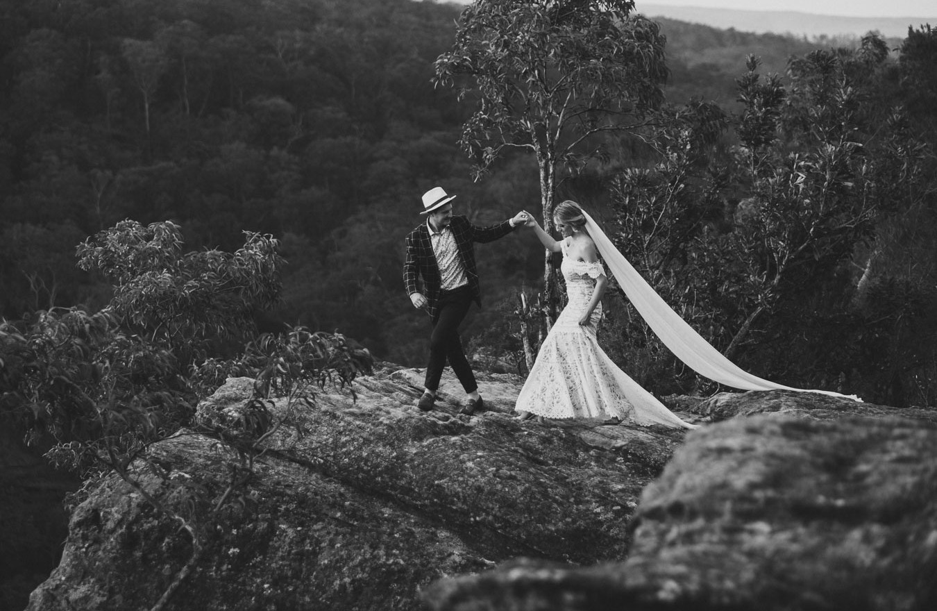 Stunning black and white wedding photography of a bride and groom walking on a cliff top.