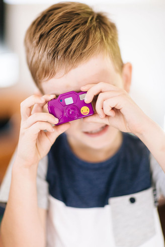 Fun family photography of a boy and his toy camera.