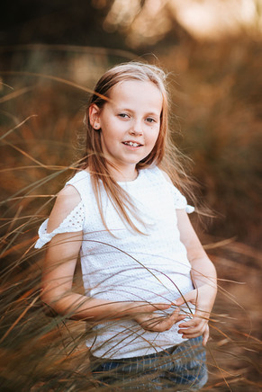 Sydney childrens photography of a child in a grass field at sunset.