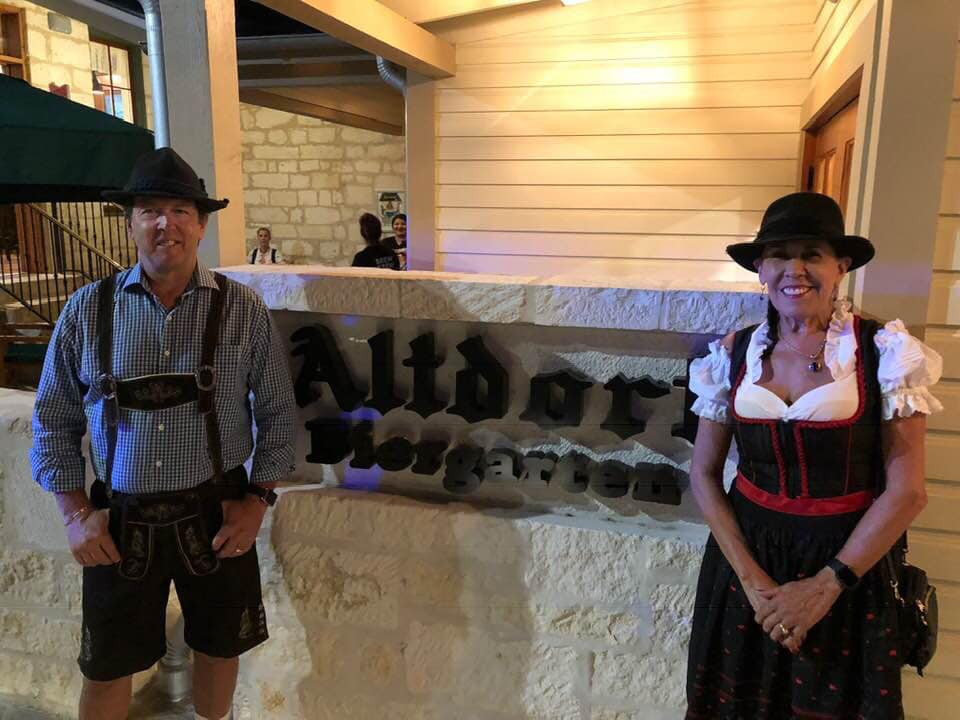 Owners Gary and Maggie Klenzing standing in front of sister restaurant Altdorf Biergarten in their traditional German clothing after visiting Oktoberfest!