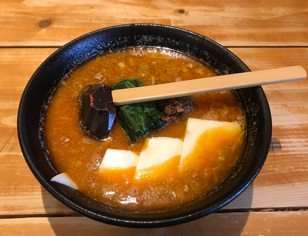 Bowl of ramen with cheese slices and spinach, on a wooden background.