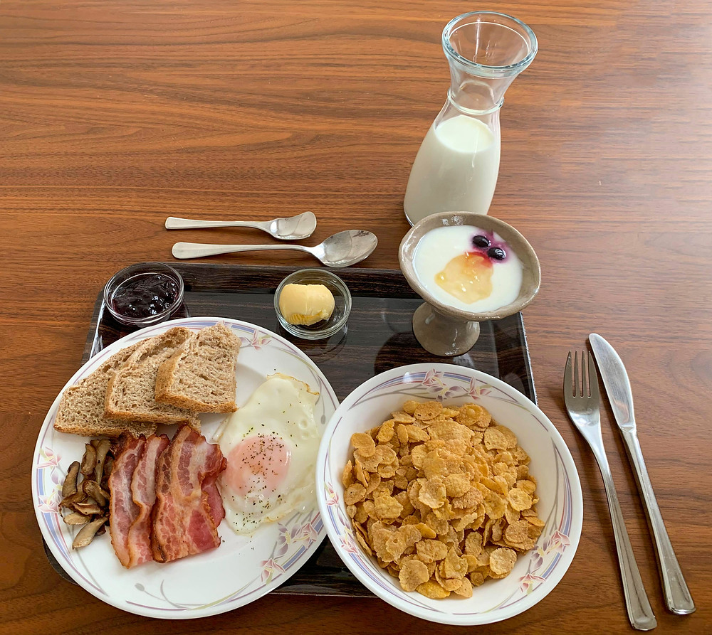 Breakfast set with bacon, eggs, fresh bread, cereal, yogurt and Hokkaido milk and butter.