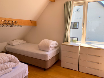 The bedroom has two beds on each side of the window.