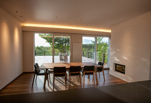 Dining room with fireplace and balcony views.